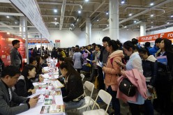 Job applicants consult recruitment information at a labor market on Feb. 27, 2016 in Dalian, Liaoning Province.