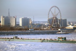 A distant view of an amusement park in Heihe, Heilongjian, China, on the southern bank of the Amur River, as seen from Blagoveshchensk, Amur Region, Russia.