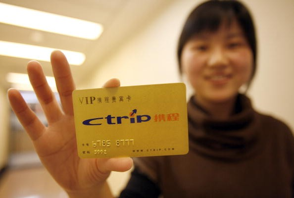 A woman displays a Ctrip.com International Ltd. membership card in Shanghai, China.