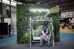 An attendee sits in front of a signage for smartphone maker Oppo at the Mobile World Congress Shanghai in Shanghai, China.