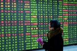 An investor watches the electronic board at a stock exchange hall on Feb. 3, 2017 in Hangzhou, Zhejiang Province.