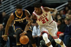 Jimmy Butler of the Chicago Bulls and Paul George of the Indiana Pacers chase down a loose ball at the United Center on December 26, 2016 in Chicago, Illinois.