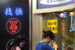 People line up at a currency changer in Hong Kong.