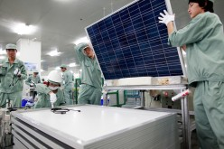 Employees assemble photovoltaic panels at Suntech Power Holdings Co.'s factory in Wuxi, Jiangsu Province.