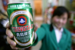 A can of Tsingtao beer is displayed by a clerk at a food market.