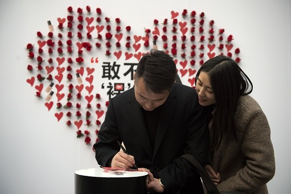A couple write on a heart-shaped sticker at a shopping mall on Valentine's Day in Beijing.