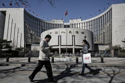 Pedestrians walk in front of the People's Bank of China headquarters in Beijing.