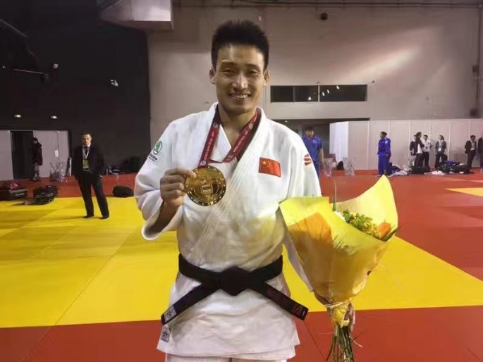 Judoka Cheng Xunzhao showing his gold medal from the Paris Grand Slam.