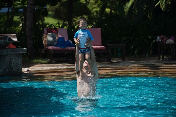A man lifts a boy up in the air in a pool at the Club Med resort in Sanya, which was bought by Fosun in 2015.