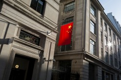 The Chinese national flag hanging in sunshine from the Bank of China's headquarters in the City of London, United Kingdom.