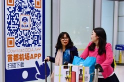 Two Chinese women arrive at Beijing Capital International Airport as they cart purchased goods from abroad.