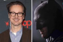 Director Matt Reeves smiles for the camera alongside a photo of Ben Affleck as Batman.