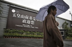 A man holding an umbrella walks past a welcome sign for Yuhuang Shannan Fund Town in Hangzhou, China.