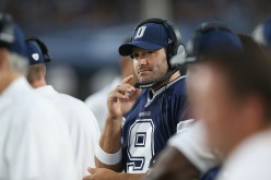 Quarterback Tony Romo #9 of the Dallas Cowboys works with a headset on the sidelines against the Los Angeles Rams at the Los Angeles Coliseum during preseason