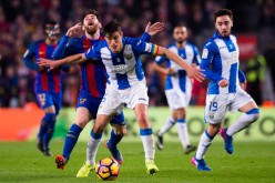 Leganes captain Martin Mantovani (#5) competes for the ball against Barcelona's Lionel Messi.
