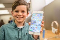Levi aged 10, shows of the new iPhone 6s Plus in rose gold as crowds wait in anticipation for the release of the iPhone 6s and 6s Plus at Apple Store.