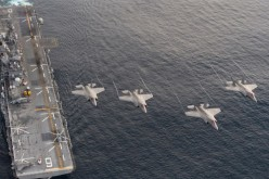Four F-35B Lightning II aircraft perform a flyover above the amphibious assault ship USS America (LHA 6).