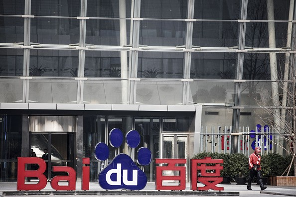 A man walks past a sign for Baidu Inc. at the entrance to the Baidu Technology Park in Beijing, China.