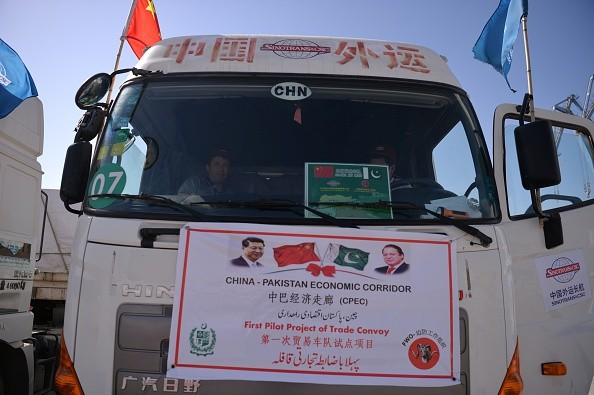 Chinese workers sit in trucks carrying goods during the opening of a trade project in Gwadar port, some 700 km west of the Pakistani city of Karachi.