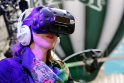 A visitor tries the virtual reality headset HTC Vive to experience 3D virtual reality during the show