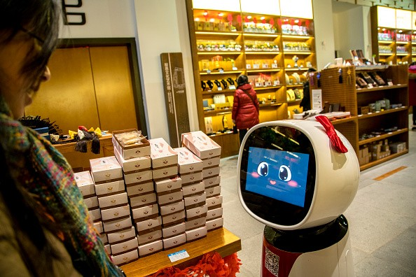 An AI robot is selling souvenir goods in a tourist shop. Besides introducing the information of goods, she can also interact and respond with voice appropriately with customers.