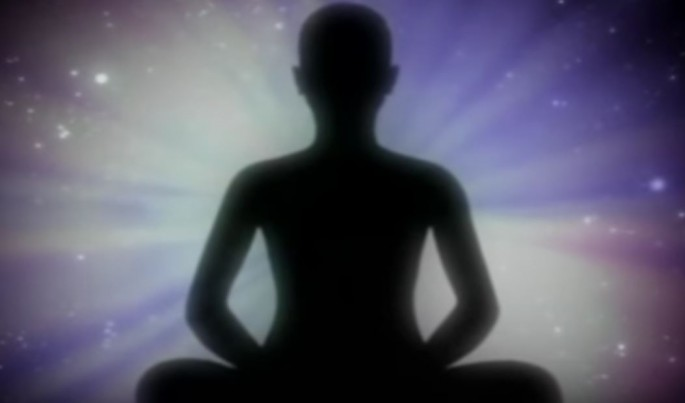 A shadow of man is displayed while he meditates.