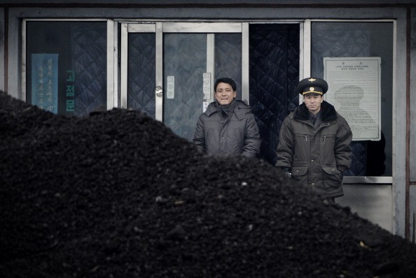 North Korean military officer (R) and a North Korean man (L) standing behind a pile of coal along the banks of the Yalu River northeast of the North Korean border town of Siniuju.