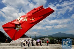 Tourists stand beside a monument to Communist partisans in Jinggangshan, Jiangxi Province, China.