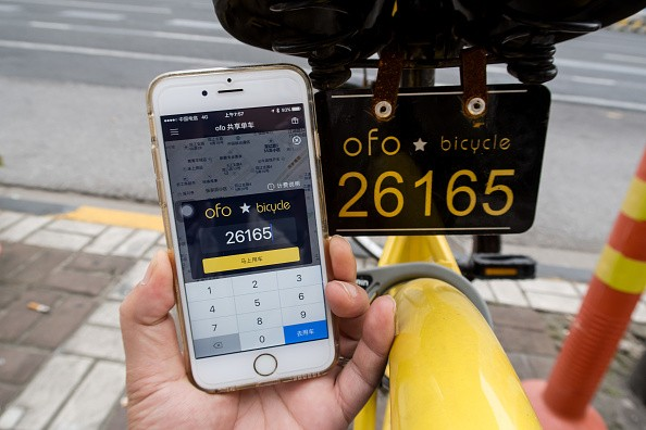 A passenger uses app on the phone to check mileage of a yellow rental bike at the service points of Zhoujiazui Road.