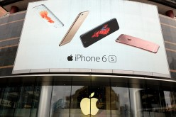 A billboard showing Apple phones is seen at an Apple Store in Beijing, China.