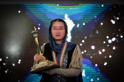Chinese chess player Tan Zhongyi holds her trophy after she won the Women's World Chess Championship 2017.
