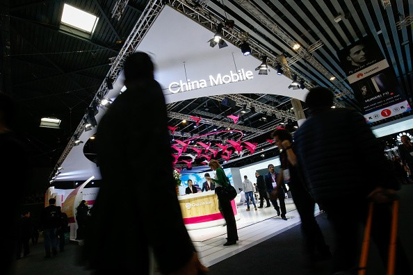 An attendee uses a mobile device as she passes the China Mobile stand on the second day of the 2017 Mobile World Congress (MWC) in Barcelona, Spain.