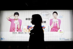 A commuter walks past a China Mobile Ltd. advertisement in the Futian district of Shenzhen, China.