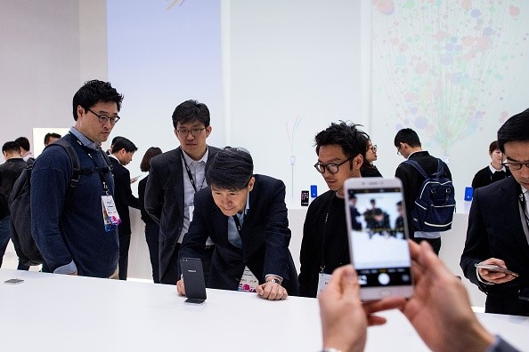 Visitors look at Oppo devices during the Mobile World Congress 2017