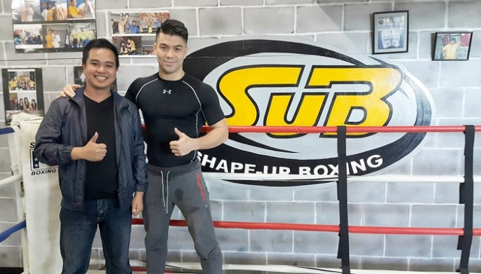 Filmmaker Conan Altatis poses with MMA fighter Mark Striegl in Shape-Up Boxing Gym in Baguio City, Philippines.