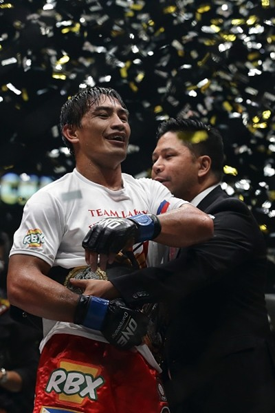 Eduard Folayang receives the championship belt from One FC CEO Victor Cui after defeating Shinya Aoki for the men's lightweight world championship bout during 'One Championship: Defending Honor' on Nov. 11, 2016 in Singapore.