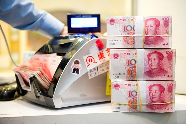 An employee counts Chinese Yuan bank notes in a Standard Chartered bank branch in Shanghai, China.