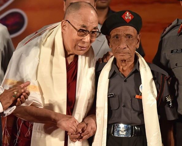 Tibetan spiritual leader the Dalai Lama (L) shakes hands with retired Assam Rifles personnel Naren Chandra Das.