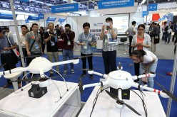 People crowd to view an exhibit on unmanned aerial vehicle models at the Aviation Expo China.