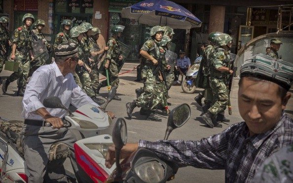 Chinese soldiers march past the Id Kah Mosque, China's largest, on July 31, 2014, in Kashgar, China.