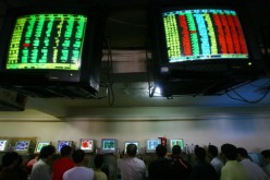 Investors view stock prices displayed on computers at a securities company, June 25, 2007, in Chongqing Municipality, China.