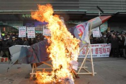South Korean protesters burn an effigy of a North Korean missile.