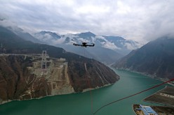 A drone towing a cable flies over the Dadu River to another side of the Ya'an-Kangding expressway bridge being built on Dec. 20, 2016 in Ya'an, Sichuan Province of China.