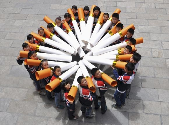 Students pose for pictures with ''big cigarette models'' for a campaign.
