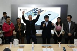 Apple Inc.'s CEO Tim Cook next to tech representatives from China at Apple store.