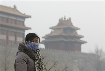 A visitor wears a mask outside the Forbidden City due to heavy air pollution.
