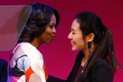 First Lady Michelle Obama (L) is greeted before a presentation on free speech at Peking University.