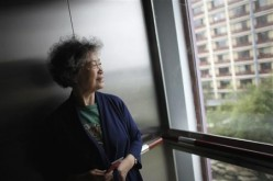 Zhu Yuefeng, 75, stands in the elevator of her apartment building.