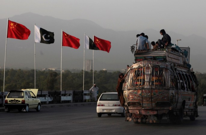 People sit on top of a bus as they go past flags of Pakistan and China displayed along a road in Islamabad.