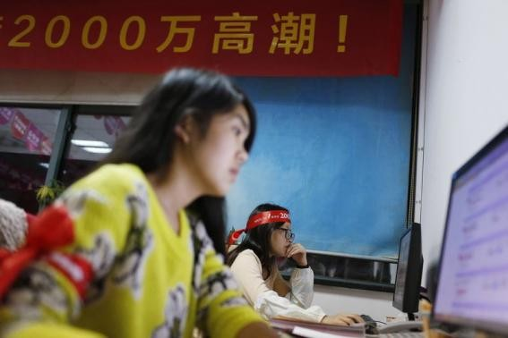 Employees of Tmall, part of Alibaba, work online to serve customers.